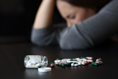 woman and benzodiazepine pills on a counter