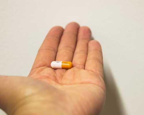 Man holding an addictive Adderall pill