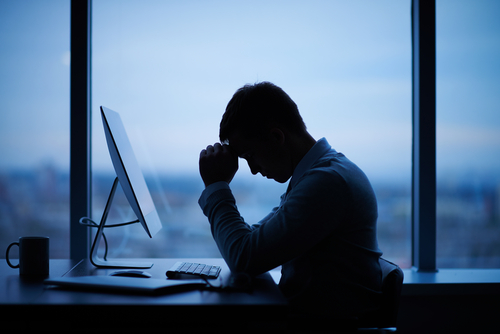 Sad alcoholic man in front of computer