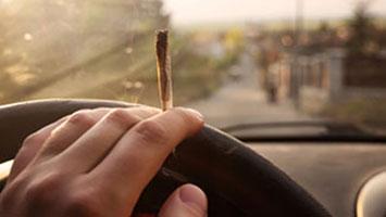 Person smoking marijuana, a low level drug offense.