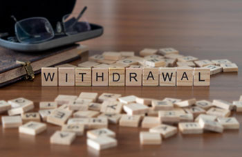 """""""Withdrawal"""" spelled out in wooden tiles"""