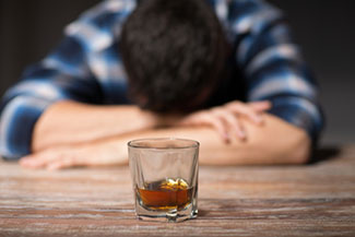 Alcoholic man passed out in front of a glass of dark liquor.