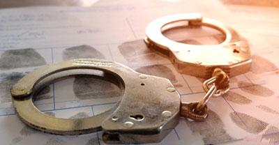 A felon's record underneath a pair of handcuffs